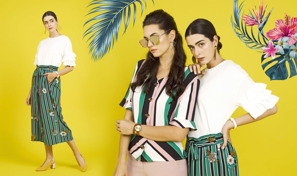 one woman wearing green palazzo pants & white top and another woman wearing dusty pink and green striped blouse