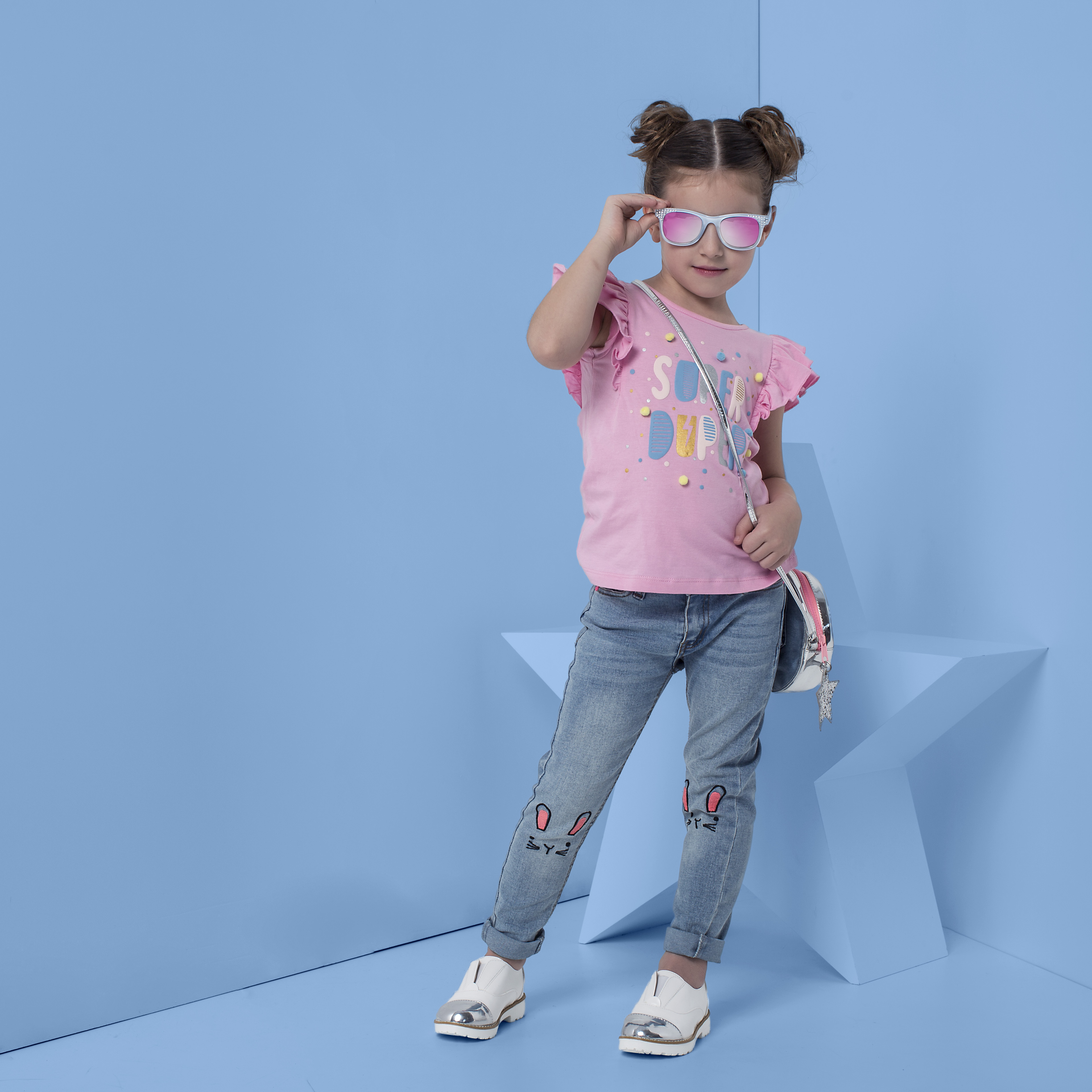 Junior girl wearing a pink t-shirt and embroidered jeans