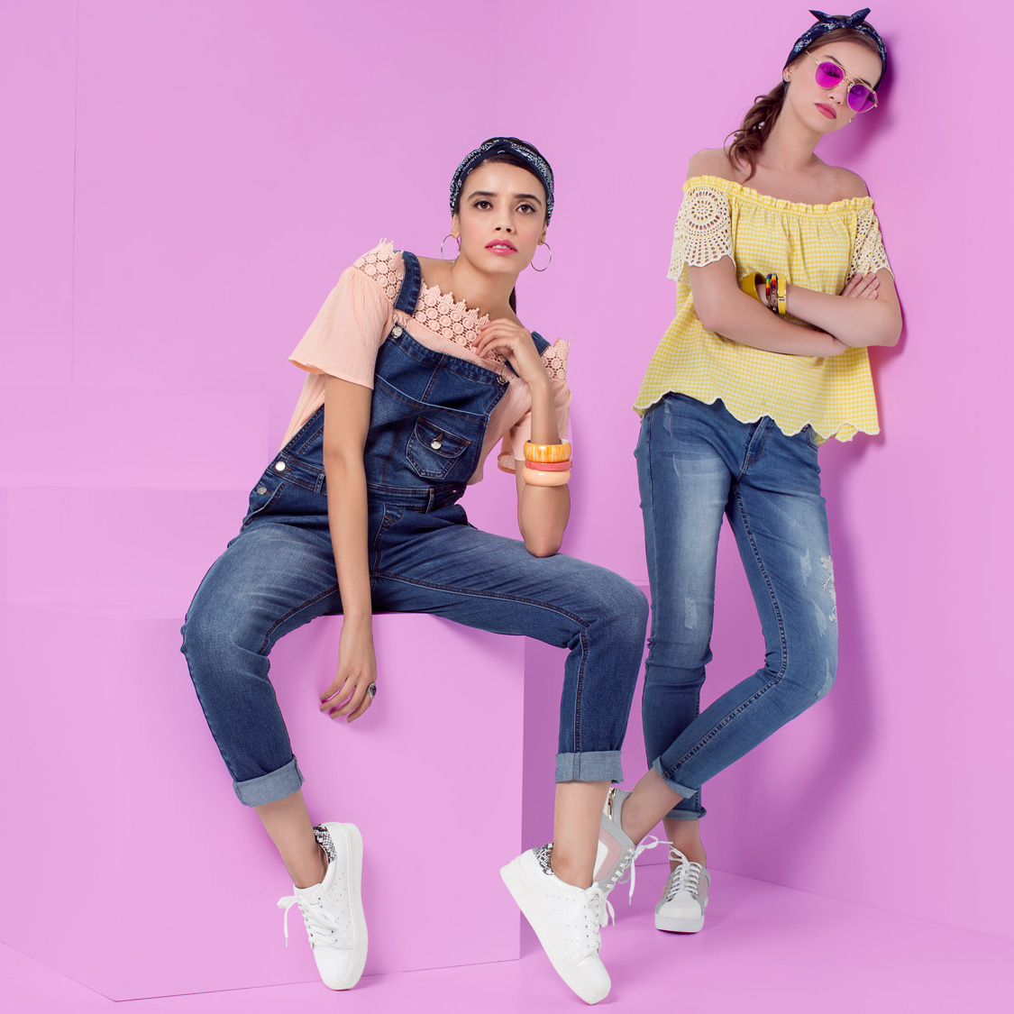 Two women, one wearing a pastel top & a dungaree and another one wearing yellow top with jeans